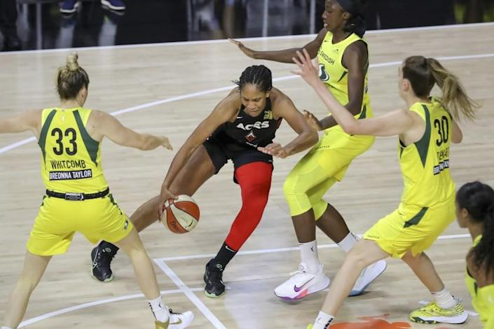 "Aces forward A'ja Wilson drives against the Storm defenders (from left) Sami Whitcomb, Natasha Howard and Breanna Stewart during a game in the WNBA bubble. <span class=""copyright"">(Mike Carlson / Associated Press)</span>"