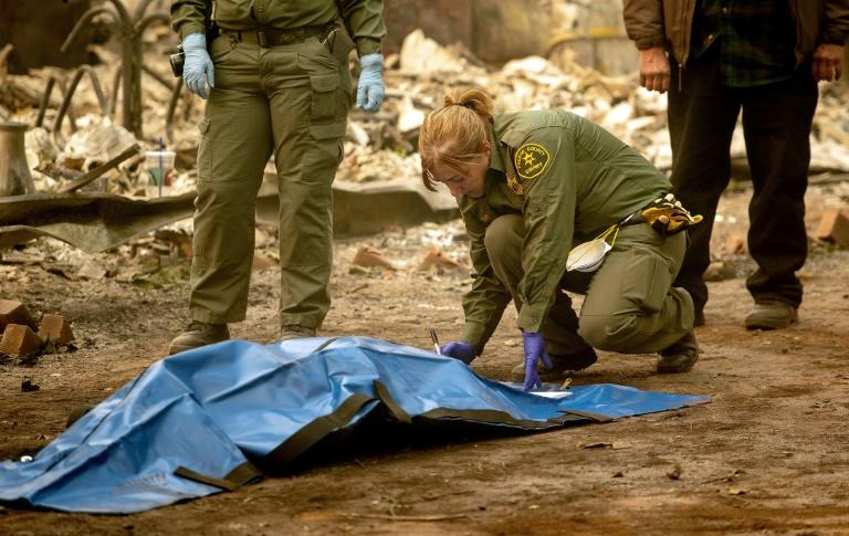 A Fresno County Sheriff's officer tends to a body recovered at a burned residence in Paradise, California