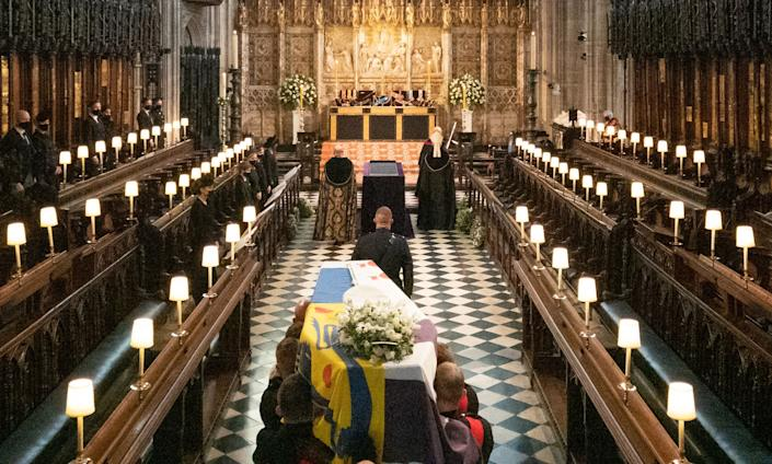 The coffin is carried into the quire during the funeral service.