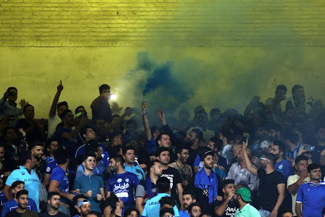 Only men are allowed to attend soccer matches in Iran, so women disguise themselves as men to attend. (Atta Kenare/AFP)