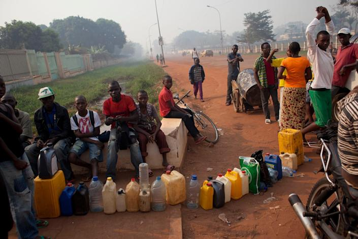 People queuing to purchase fuel hold their places in line with jerrycans at a gas station that was closed, as they await the arrival of military police, in Bangui, Central African Republic, Tuesday, Dec. 24, 2013. With few gas stations open and reliable fuel hard to find, people lined up as early as 4 a.m. at this station, which wasn't slated to open until police protection arrived around 9 or 10 a.m. (AP Photo/Rebecca Blackwell)