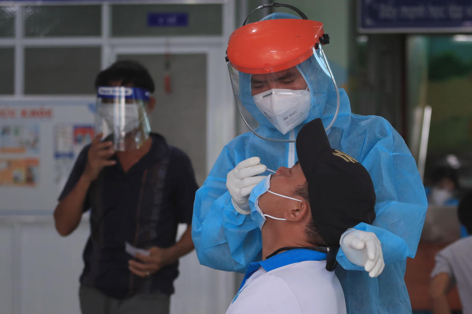 A medical worker takes swab sample from a man in Vung Tau city, Vietnam Saturday, Aug. 21, 2021. Vietnam's government said it is sending troops to Ho Chi Minh city to help deliver food and aid to households as it further tightens restrictions on people's movements amid a worsening surge of the coronavirus. (AP Photo/Hau Dinh)