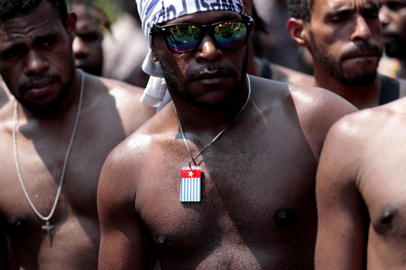 A Papuan activist wears a necklace separatist 'Morning Star' flag during a rally near the presidential palace in Jakarta, Indonesia, Thursday, Aug. 22, 2019. A group of West Papuan students in Indonesia's capital staged the protest against racism and called for independence for their region. (AP Photo/Dita Alangkara)