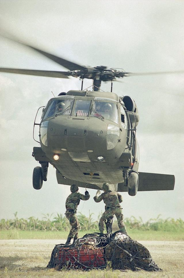 <p>A Blackhawk helicopter hovers over two members of the 49th Quartermaster Detachment from Fort Bragg, N.C., as they attach a sling to it, carrying supplies for victims of Hurricane Andrew, Sept. 11, 1992, at the Homestead Humanitarian Depot. (AP Photo/Kathy Willens) </p>