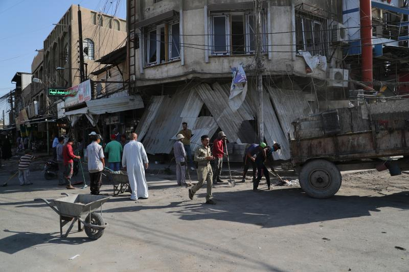 Municipality workers clean up as civilians inspect the aftermath a day after a motorcycle rigged with explosives exploded in Mussayyib, south of Baghdad, Iraq, Saturday, Aug. 24, 2019. The officials said Saturday that the blast occurred the previous evening on a commercial street in the village of Mussayyib, killing and wounding civilians. (AP Photo/Khalid Mohammed)