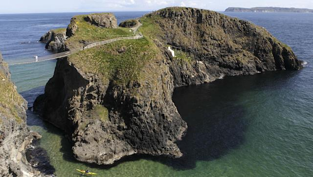 Denis Broderick, left, carries the Olympic Torch over the Carrick-a-Rede rope bridge in county Antrim, Northern Ireland, Monday, June 4, 2012. The Olympic Torch is continuing its relay journey around the country, and is scheduled to arrive at the opening ceremony of the London 2012 Olympic Games. (AP Photo/Peter Morrison)