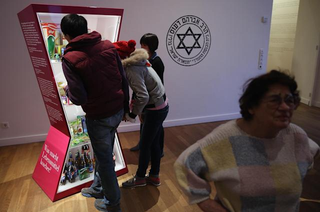 "BERLIN, GERMANY - APRIL 04: Visitors look at an exhibit of kosher food at the exhibition ""The Whole Truth - Everything You Always Wanted To Know About Jews . . . "" at the Juedisches Museum (Jewish Museum) on April 4, 2013 in Berlin, Germany. The exhibition presents every-day aspects of Jewish life, poses simple questions answered with exhibits and challenges certain stereotypes. However its live exhibit, which features a Jewish person who sits in a plastic enclosure open on one side for several hours a day to answer visitors' questions, has sparked criticism from some Jewish groups. (Photo by Sean Gallup/Getty Images)"