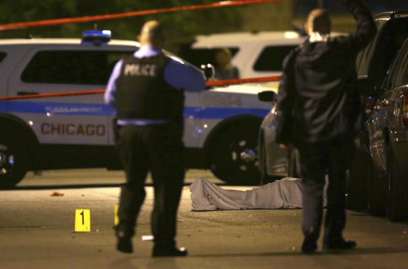 FILE - In this May 30, 2016 file photo, police work the scene where a man was fatally shot in the chest in Chicago. Chicago's Police Superintendent Eddie Johnson visited New York to learn how it has achieved success in fighting crime. Johnson came home with ideas aimed at increasing community trust by using technology to get Chicago police officers out of their squad cars and putting new cadets in neighborhoods to walk the streets. (E. Jason Wambsgans/Chicago Tribune via AP)