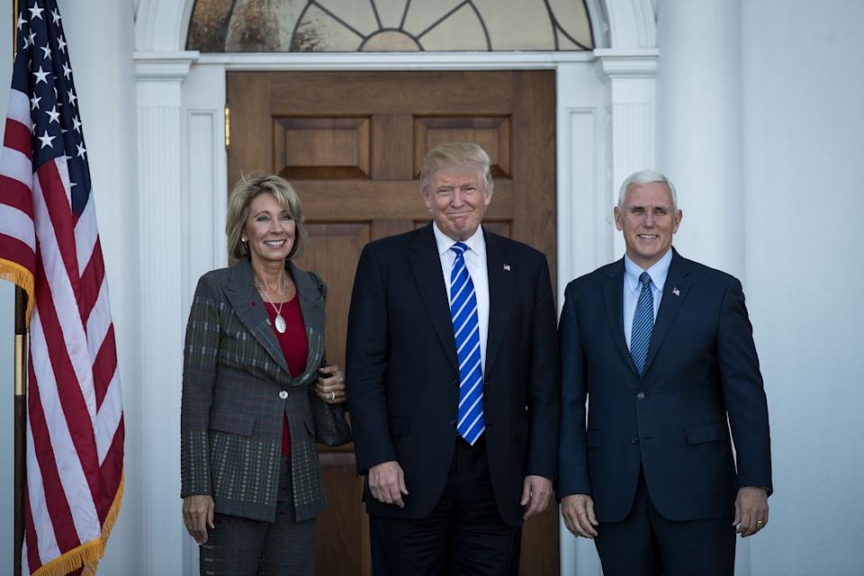 Education Secretary Betsy DeVos poses with Donald Trump and Mike Pence