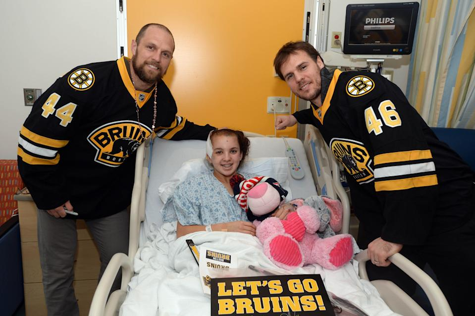 In this Feb. 5, 2015 photo, David Krejci, right, and Dennis Seidenberg of the NHL's Boston Bruins visit with a girl named Carly at Boston Children's Hospital.
