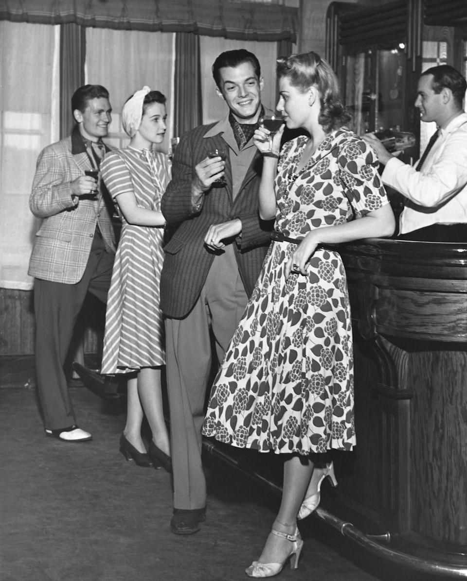 """<p>Men and women socialize at a classic bar, now referred to as the """"retro style."""" Many of these bars are still around today as vintage, old time diners. </p>"""
