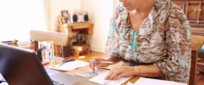 Woman crunches numbers for her emergency fund in her home office.
