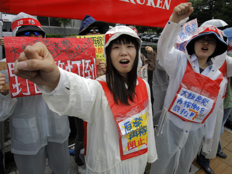 """Demonstrators raise clenched fists during a rally, protesting against restarting the Ohi nuclear power plant's reactors in front of the prime minister's official residence in Tokyo, Saturday, June 16, 2012. Japan moved closer to restarting the nuclear reactors for the first time since last year's earthquake and tsunami led to a nationwide shutdown. A slogan, center, reads: """"Stop restarting nuclear power plant."""" (AP Photo/Itsuo Inouye)"""
