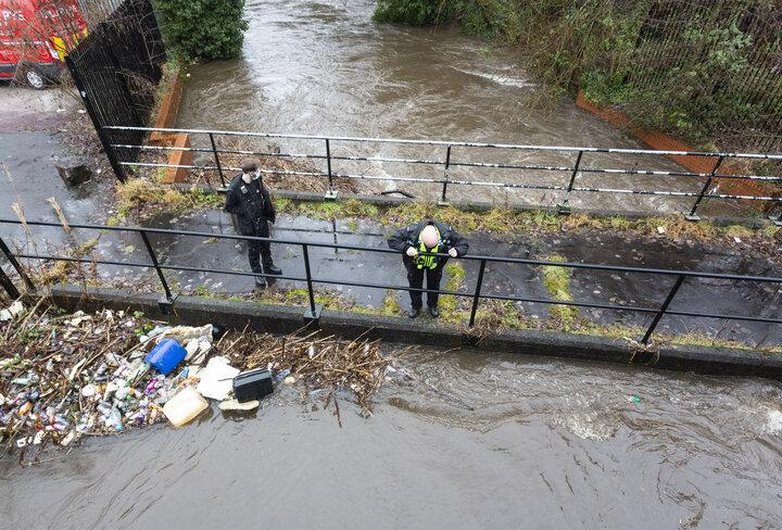 Police officers patrol a submerged bridge along the River Roch, in Greater Manchester.