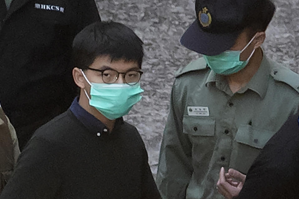 Hong Kong activist Joshua Wong is escorted by Correctional Services officers to get on a prison van before appearing in a court, in Hong Kong, Wednesday, Dec. 2, 2020. Prominent Hong Kong pro-democracy activist Wong and two other activists, Lam and Agnes Chow, were taken into custody after they pleaded guilty to charges related to a demonstration outside police headquarters during anti-government protests last year. (AP Photo/Kin Cheung)