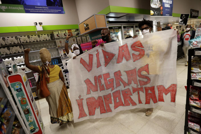 """Holding the Portuguese message """"Black Lives Matter,"""" activists demonstrate against the murder of Black man João Alberto Silveira Freitas, which occurred the night before at a different Carrefour supermarket, on Brazil's National Black Consciousness Day in Brasilia, Brazil, Friday, Nov. 20, 2020. Freitas died after being beaten by supermarket security guards in the southern Brazilian city of Porto Alegre, sparking outrage as videos of the incident circulated on social media. (AP Photo/Eraldo Peres)"""