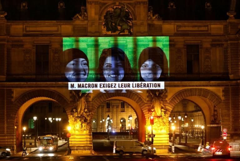 Amnesty International projects images of jailed Saudi activists including Loujain al-Athloul on the Louvre Museum in Paris
