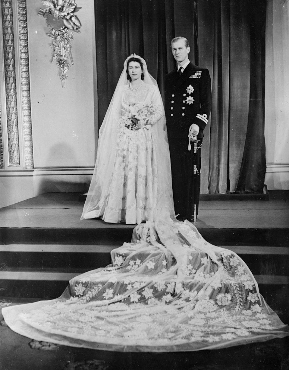 "<p>The Queen married Philip Mountbatten in a long-sleeve <a href=""https://www.townandcountrymag.com/society/tradition/a13438510/queen-elizabeth-wedding-dress/"" rel=""nofollow noopener"" target=""_blank"" data-ylk=""slk:pearl-embellished"" class=""link rapid-noclick-resp"">pearl-embellished</a> gown and matching veil. She saved up for the dress using ration coupons, due to the post-WWII economy, <em><a href=""https://www.townandcountrymag.com/society/tradition/a13438510/queen-elizabeth-wedding-dress/"" rel=""nofollow noopener"" target=""_blank"" data-ylk=""slk:Town & Country"" class=""link rapid-noclick-resp"">Town & Country</a></em> reports.</p>"