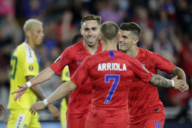 United States' Tyler Boyd, facing camera, celebrates with teammates Paul Arriola (7) and Christian Pulisic (10) as Guyana's Matthew Briggs (20) walks away during the second half of a CONCACAF Gold Cup soccer match Tuesday, June 18, 2019, in St. Paul, Minn. (AP Photo/Andy Clayton-King)