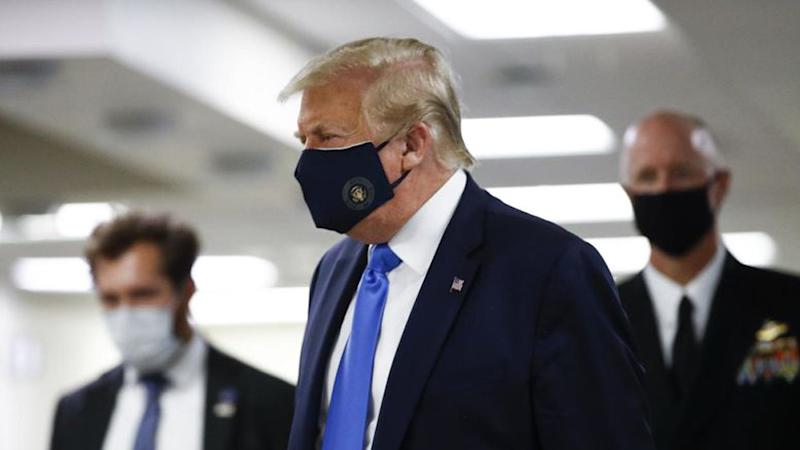 President Donald Trump wearing a face mask while visiting a hospital