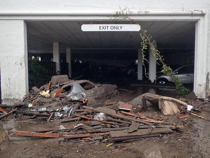 <p>Damaged vehicles carried by mud flow and debris at the parking garage of The Montecito Inn in Montecito, Calif., Tuesday, Jan. 9, 2018. (Photo: Mike Eliason/Santa Barbara County Fire Department via AP) </p>