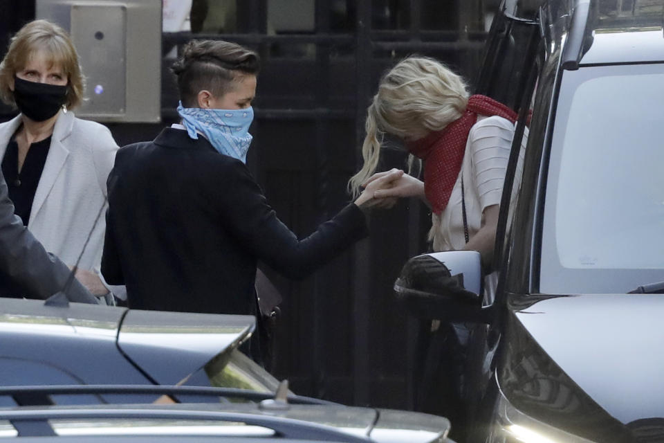 American actress Amber Heard, right, gets out of a vehicle and holds the hand of her girlfriend Bianca Butti as they arrive at the High Court in London, Monday, July 20, 2020. Amber Heard started Monday to give evidence at the High Court in London as part of Johnny Depp's libel case against The Sun over allegations of domestic violence during the couple's relationship. (AP Photo/Matt Dunham)