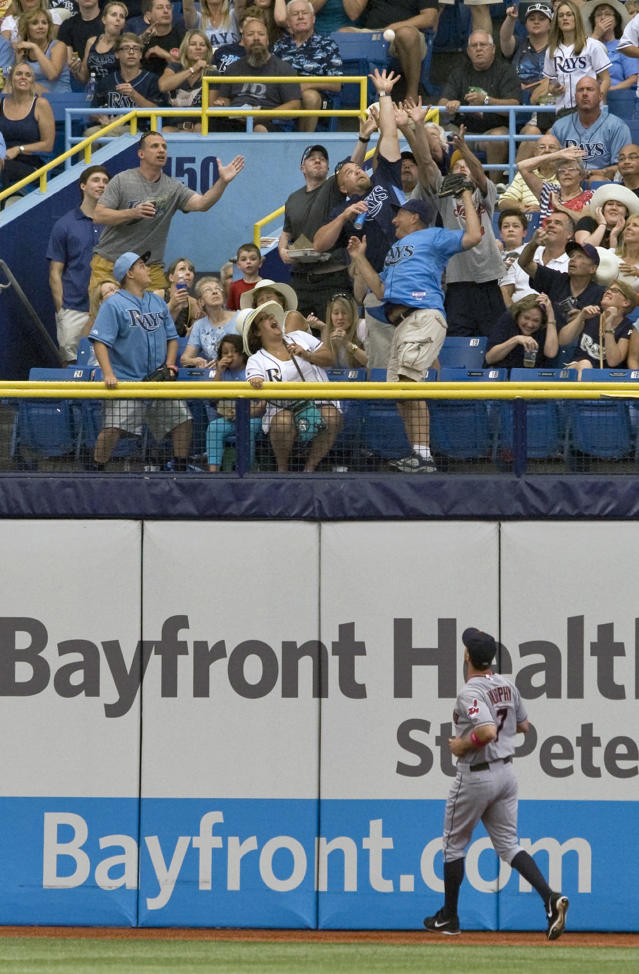 Cleveland Indians right fielder David Murphy (7) looks on as fans reach for a solo home run hit by Tampa Bay Rays' Matt Joyce during the first inning of a baseball game on Sunday, May 11, 2014, in St. Petersburg, Fla. (AP Photo/Steve Nesius)