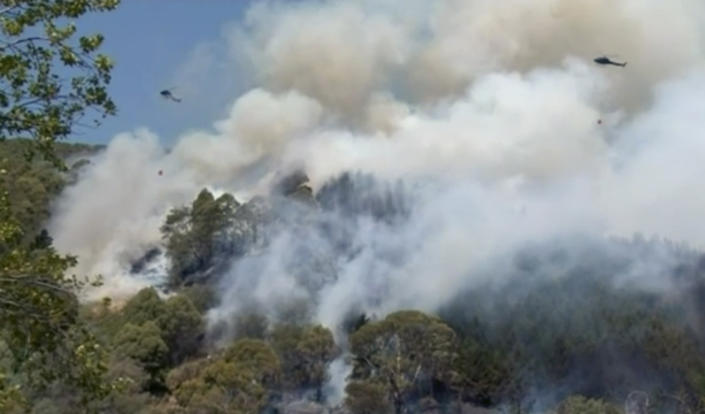 In this image made from video, helicopters drop water on a wildfire coming over a ridge near a residential area, Friday, Feb. 8, 2019, in Wakefield, New Zealand. About 700 residents were evacuated from a New Zealand town on Friday as a forest fire threatened the area. (Newshub via AP)