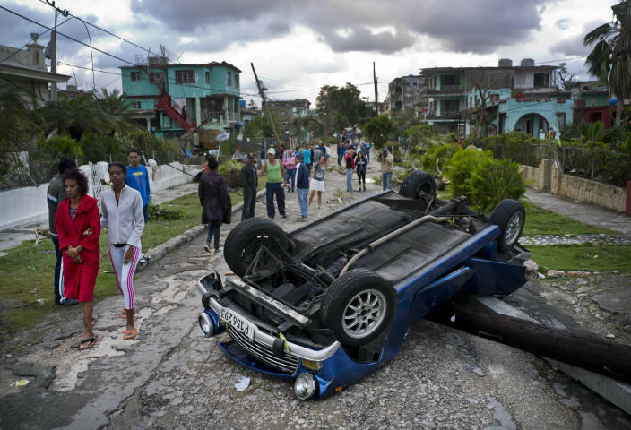 A car overturned by a tornado lays smashed on top of a street pole in Havana, Cuba, Monday, Jan. 28, 2019. A tornado and pounding rains smashed into the eastern part of Cuba's capital overnight, toppling trees, bending power poles and flinging shards of metal roofing through the air as the storm cut a path of destruction across eastern Habana. (AP Photo/Ramon Espinosa)