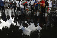 """People carrying signs supporting voting rights are reflected in a puddle as they arrive at an early voting center at Model City Branch Library, as part of a """"Souls to the Polls"""" march, in Miami, Sunday, Nov. 1, 2020. As Election Day closes in, Americans are exhausted from constant crises, on edge because of volatile political divisions and anxious about what will happen next.(AP Photo/Rebecca Blackwell)"""