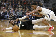 Milwaukee Bucks' Wesley Matthews (9) and Denver Nuggets' PJ Dozier dive for a loose ball during the first half of an NBA basketball game Friday, Jan. 31, 2020, in Milwaukee. (AP Photo/Aaron Gash)