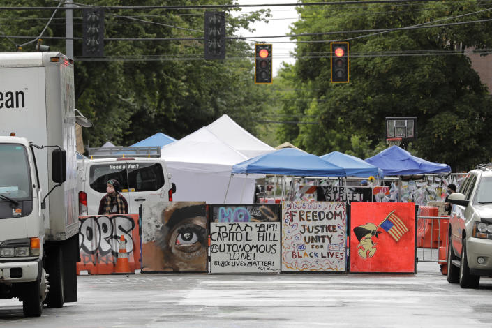 Signs are seen at an entrance, Monday, June 15, 2020, to what has been named the Capitol Hill Occupied Protest zone in Seattle. Protesters have taken over several blocks near downtown Seattle after officers withdrew from a police station in the area following violent confrontations. (AP Photo/Ted S. Warren)