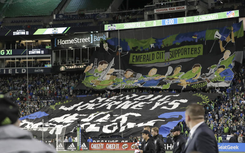 Members of the Seattle Sounders Emerald City Supporters group display a tifo before an MLS soccer match against FC Cincinnati, Saturday, March 2, 2019, in Seattle. (AP Photo/Ted S. Warren)
