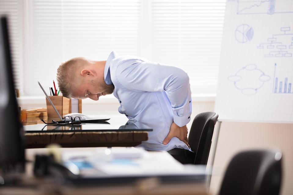 Businessman Sitting At Desk With Laptop Having Back Pain In Office