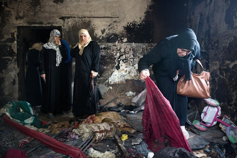 Palestinian women look at the damage at the West Bank home of the Dawabsha family on August 4, 2015 after it was firebombed by two Israeli suspects, including a minor, killing a Palestinian toddler and his parents (AFP Photo/MENAHEM KAHANA)