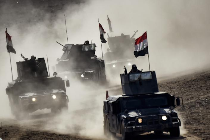 Iraqi troops advance toward Mosul in 2017 during an offensive to retake the northern Iraqi city from jihadists of the Islamic State group. (Aris Messinis/AFP via Getty Images)