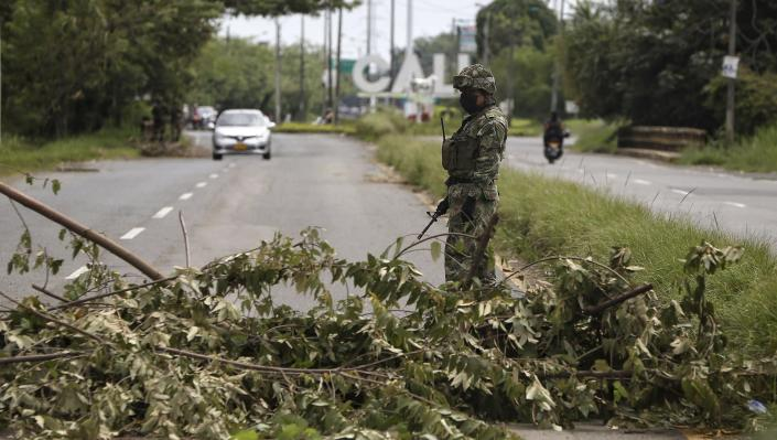 A soldier stands guard at a road block that was cleared after it was set up by anti-government protesters during a national strike in Cali, Colombia, Monday, May 10, 2021. Colombians have protested across the country against a government they feel has long ignored their needs, allowed corruption to run rampant and is so out of touch that it proposed tax increases during the coronavirus pandemic. (AP Photo/Andres Gonzalez)