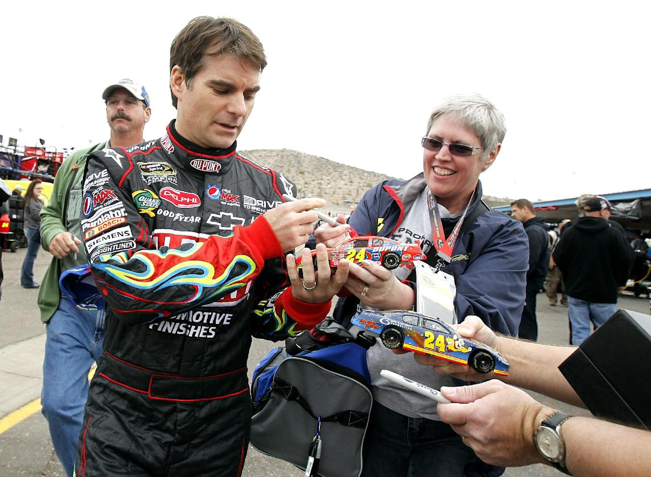 Jeff Gordon, left, signs autographs for fans in the garage area prior to NASCAR Sprint Cup practice at Phoenix International Raceway, Friday, Nov. 11, 2011, in Avondale, Ariz. (AP Photo/Ross D. Franklin)