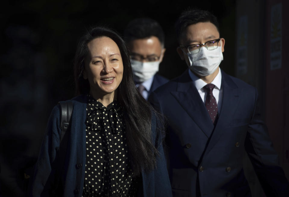Meng Wanzhou, left, chief financial officer of Huawei, leaves her home in Vancouver, on Friday, Sept. 24, 2021. U.S. prosecutors are prepared to resolve criminal charges against the chief financial officer of Chinese communications giant Huawei Technologies, the Justice Department disclosed Friday in a letter to a federal judge in New York.(Darryl Dyck/The Canadian Press via AP)