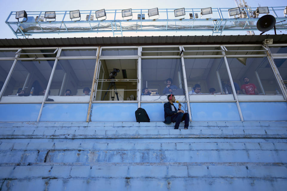 A journalist sits in Arsenal stadium as he covers Arsenal's soccer match against Defense y Justicia in a stadium devoid of fans due to COVID-19 pandemic restrictions Avellaneda, Argentina, Monday, Aug. 30, 2021. Few places in the world have soccer fans more passionate than those in Argentina, and few have been so long denied a live view of their teams due to the pandemic. (AP Photo/Natacha Pisarenko)