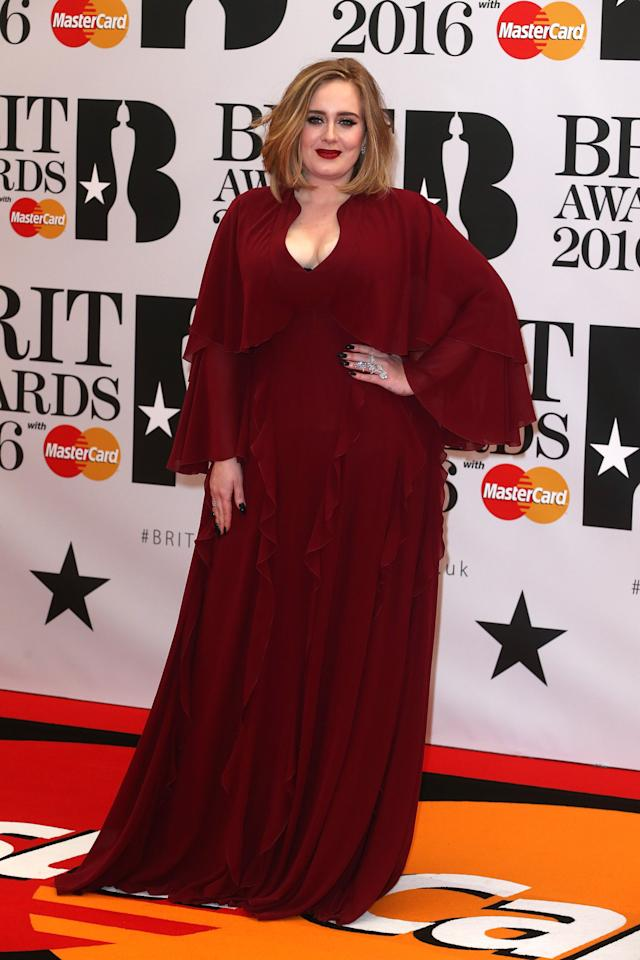<p>The songstress traded in her usual black dress for a burgundy gown with ruffles and a low-cut neckline.</p>
