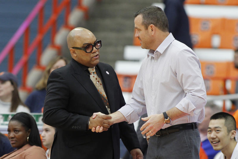 Syracuse head coach Quentin Hillsman, left, and Louisville head coach Jeff Walz, right, shake hands before an NCAA college basketball game in Syracuse, N.Y., Sunday, Feb. 9, 2020. (AP Photo/Nick Lisi)