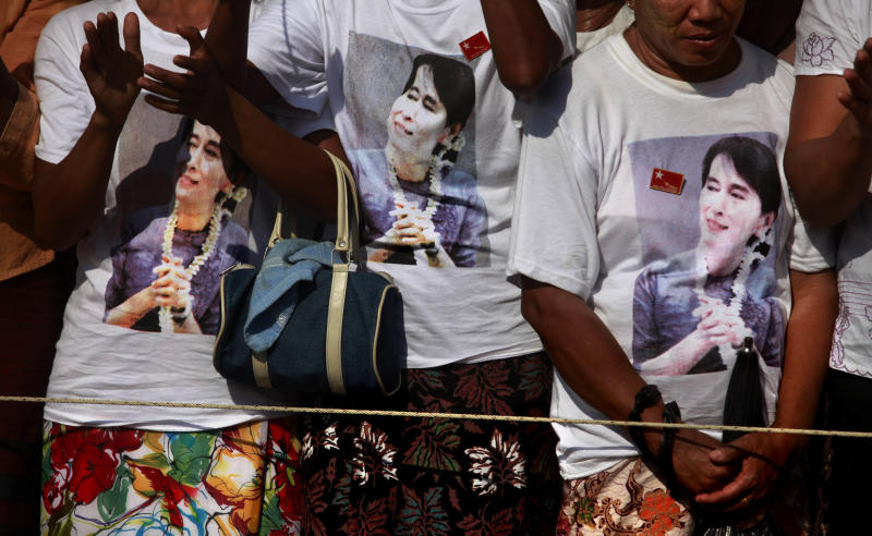 """In this photo taken, Sunday, Feb 26, 2012, supporters wearing T-shirts with the photographs of Myanmar's pro-democracy icon Aung San Suu Kyi printed on them, cheer during an election rally addressed by her in Thongwa village some 50 kilometers (31 miles) from Yangon, Myanmar. Suu Kyi's once-banished image now appears everywhere, on T-shirts, keychains and coffee mugs. Pirated copies of """"The Lady"""", the big screen version of Suu Kyi's life, are the best-selling DVD on Yangon streets. (AP Photo/Altaf Qadri)"""