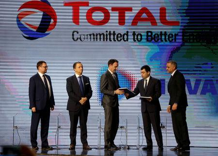 FILE PHOTO: Lebanese Energy Minister Cesar Abi Khalil hands a document to Stephane Michel, Total's head of exploration and production in the Middle East and North Africa, during Lebanon's first offshore oil and gas contract ceremony in Beirut, Lebanon February 9, 2018. REUTERS/Mohamed Azakir/File Photo