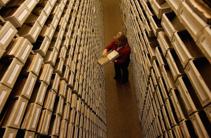 An employee of the ITS (International Tracing Service) researches documents at the Holocaust Archive on April 28, 2006 in Bad Arolsen, Germany. (Photo by Ralph Orlowski/Getty Images)