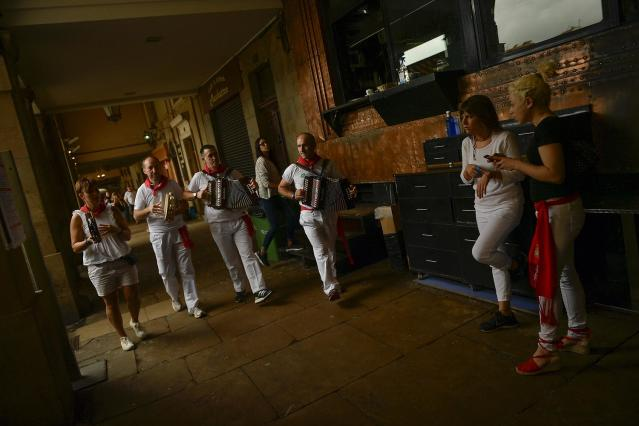 <p>Musicians dressed in white and red clothes play music along the old city at the end of the fourth running of the bulls, during the San Fermin Festival, in Pamplona, northern Spain, July 10, 2017. (AP Photo/Alvaro Barrientos) </p>