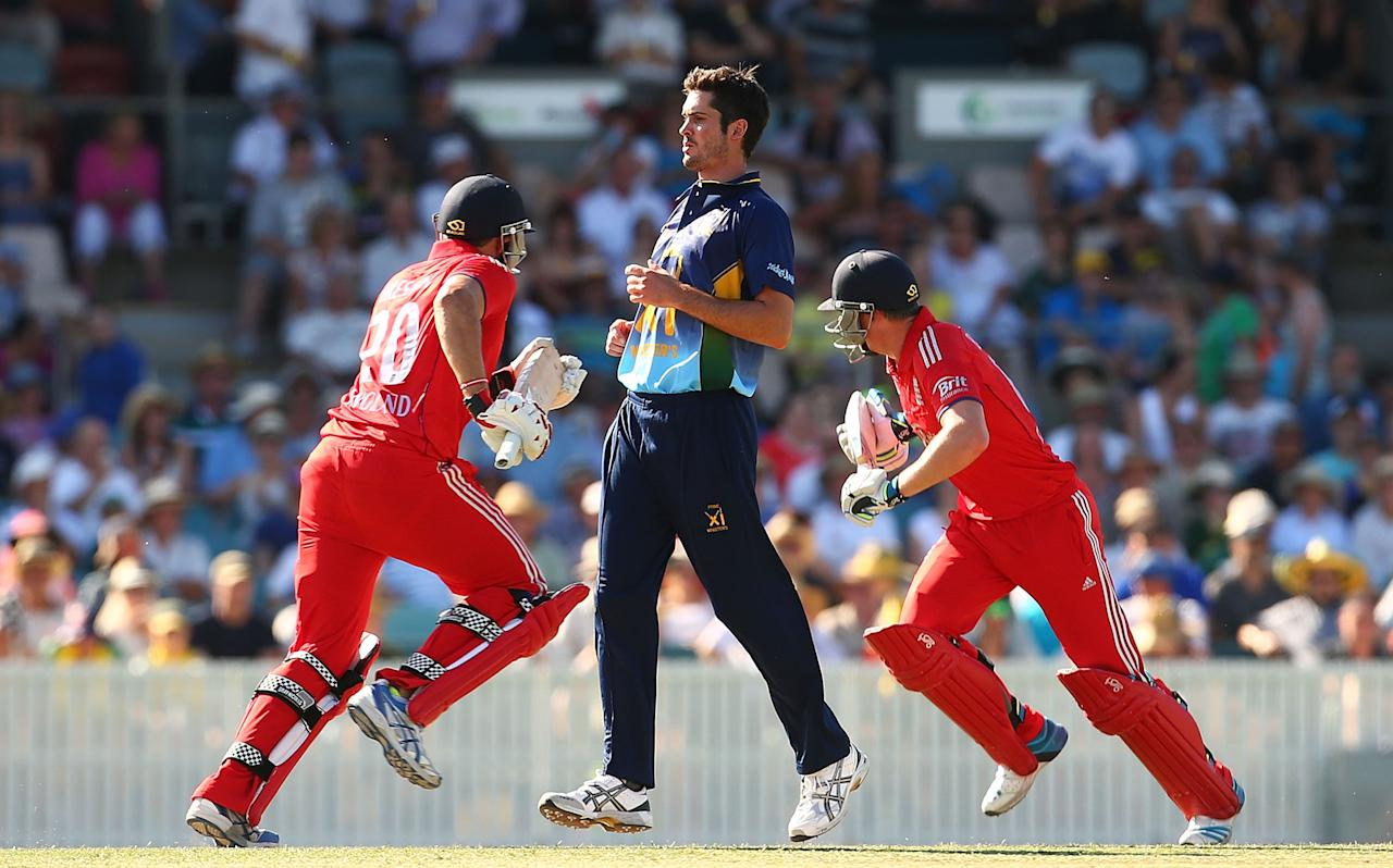 CANBERRA, AUSTRALIA - JANUARY 14: Ben Cutting of the PM's XI watches on as Tim Bresnan and Jos Buttler run between wickets during the International tour match between the Prime Minister's XI and England at Manuka Oval on January 14, 2014 in Canberra, Australia.  (Photo by Mark Nolan/Getty Images)