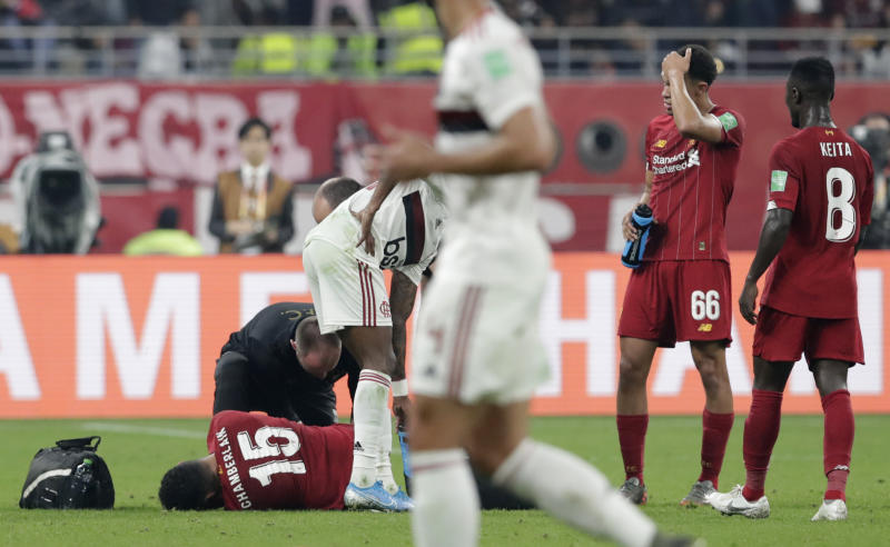 Liverpool's Alex Oxlade-Chamberlain is treated for an injury during the Club World Cup final soccer match between Liverpool and Flamengo at Khalifa International Stadium in Doha, Qatar, Saturday, Dec. 21, 2019. (AP Photo/Hassan Ammar)