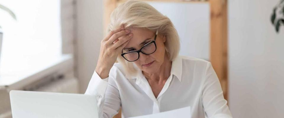 Woman looking at sheet of paper while holding her head, looking concerned