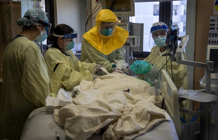 """LOMA LINDA, CA - DECEMBER 15, 2020: Pulmonologist Dr. Laren Tan, center, with his medical team of nurses and respiratory therapists intubate a COVID-19 patient who's oxygen levels were dropping in the ICU at Loma Linda University Medical Center on December 15, 2020 in Loma Linda, California. The hospital is experiencing a huge surge in COVID-19 patients. Dr. Michael Matus, chief of hospitalist said they are currently admitting more than 15 patients a day. The hospital has added 5 additional Covid units in addition to ICU. Many of the ICU patients have underlying health issues. Once those patients get Covid, """"It's a marathon that they can't run, said Dr. Tan.(Gina Ferazzi / Los Angeles Times)"""